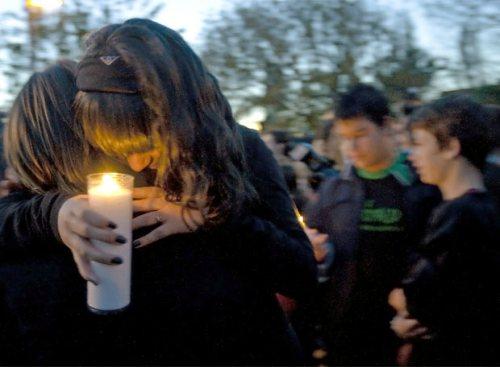 Dos jóvenes se abrazan en el funeral.
